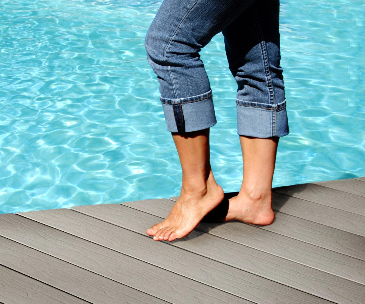 Person standing on decking by pool