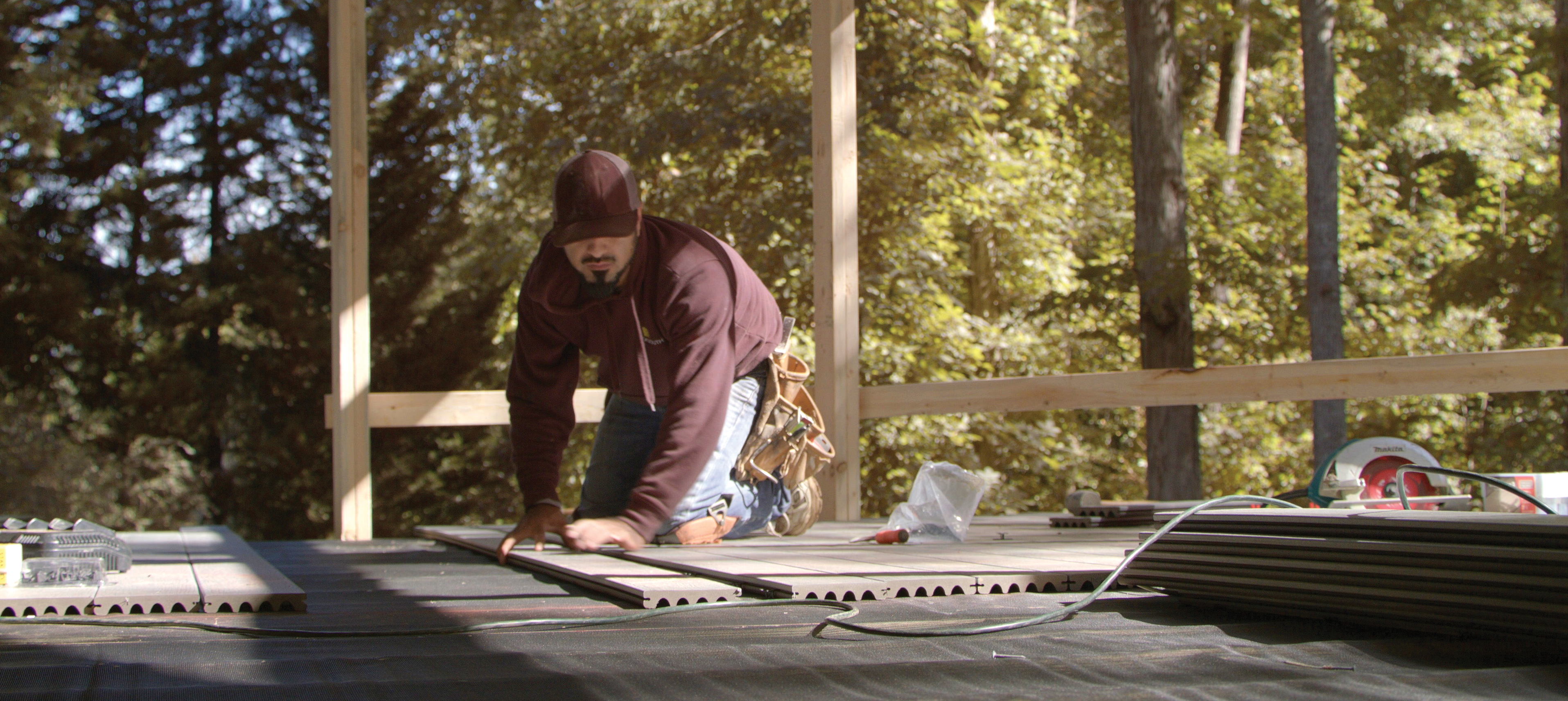 Contractor cutting composite decking boards on an existing deck.